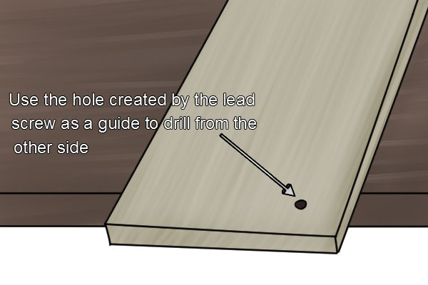 Using the hole created by the auger bits leads screw as a guide to drill from the other side of the workpiece will prevent you getting tear out of the hole.