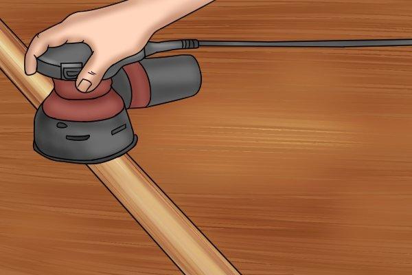 Sanding garden trowel handle with grit paper