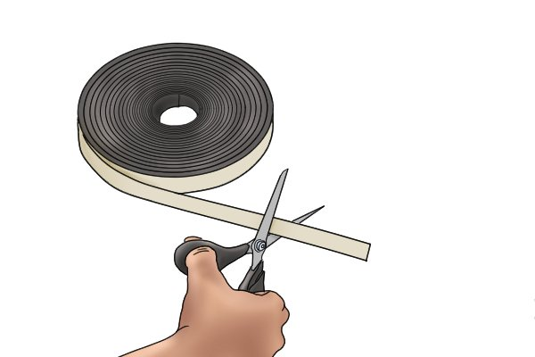 Cutting a piece of flexible magnetic tape with a pair of scissors