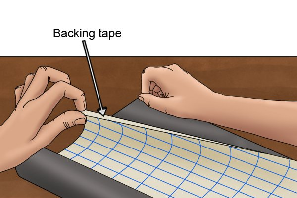 Peeling off the adhesive backing from a flexible magnetic sheet