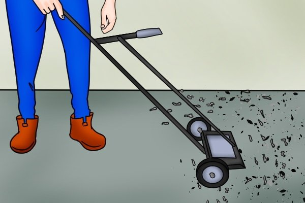 Green heavy duty push magnetic sweeper being used to pick up a pile of dropped metal