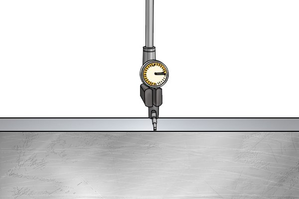 Traverse the table laterally back and forth so that the contact point of the dial indicator sweeps the surface of the fixed jaw of the vice.