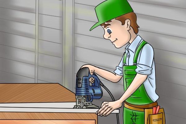 Man using jigsaw in workshop