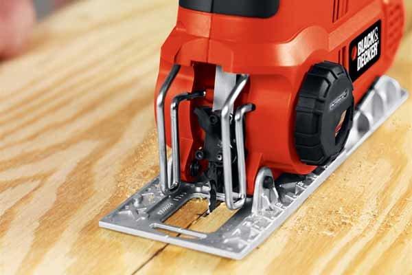 Cutting softwood with jigsaw, baseplate of jigsaw, jigsaw shoe