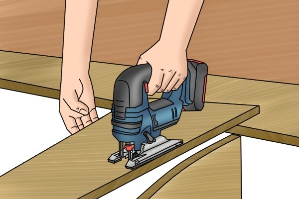 Cordless jigsaw being used to make straight cut in wood