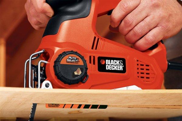Jigsaw making straight cut in wood, blade cutting through workpiece