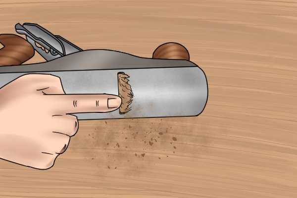 Mouth of hand plane choked with shavings