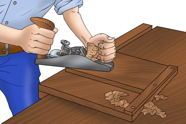 Planing the edge of piece of wood; woodworking planes