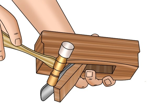Adjusting the blade of a wooden hand plane with a mallet