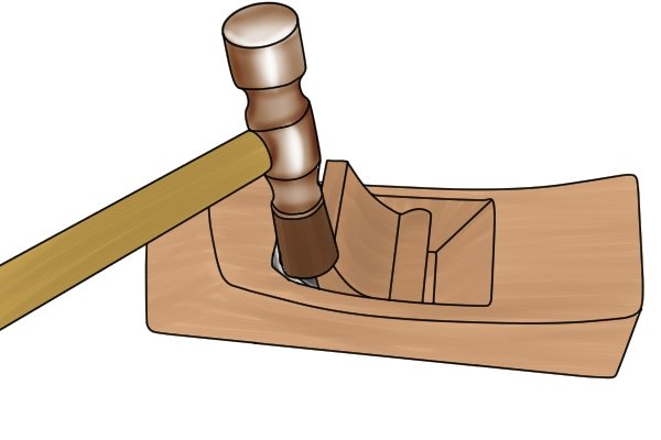 Tapping the wedge to secure the iron of a wooden hand plane