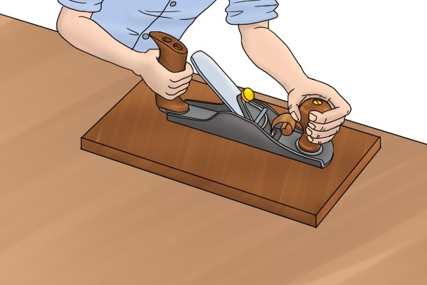 Thicknessing a piece of wood with a scrub plane; woodworking hand plane