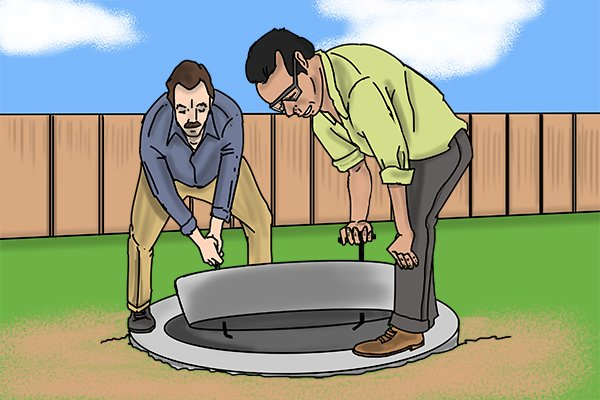 Two men lifting a manhole cover with manhole keys safely