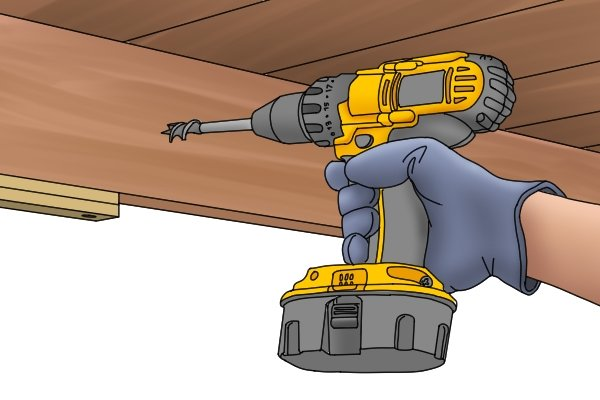 A DIYer drilling through a wooden rafter to install a cable