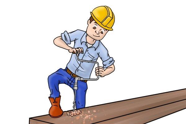 A builder using an auger bit on a construction site