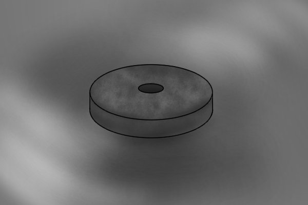 A circular piece of graphite with a hole through the centre by a brad point bit