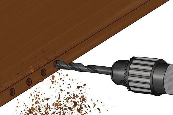 Image of a DIYer using a brad point bit to drill a hole for a dowel