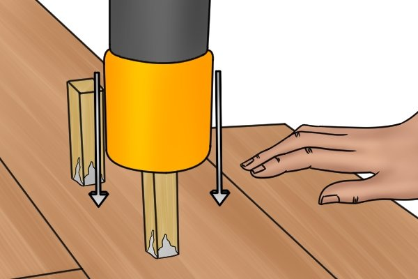 DIYer hammering a dowel into a drawbored mortise and tenon joint using a rubber tipped hammer