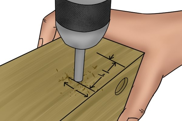DIYer using a brad point bit to drill through a mortise to create a dowel hole for a drawbore