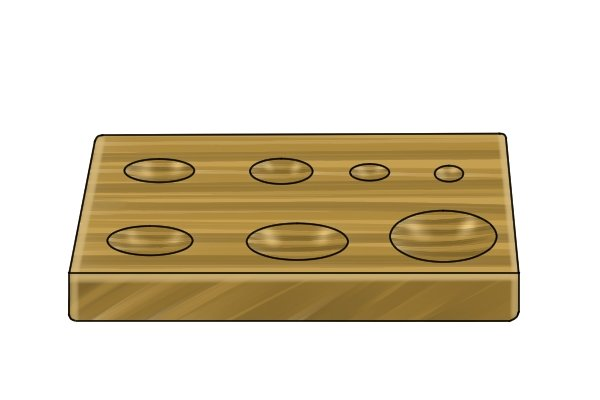 Round-bottomed holes that have been drilled into a wooden workpiece using a spoon bit