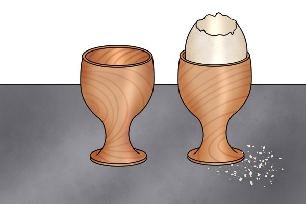Image of two wooden egg cups with visible round-bottomed bore holes that have been created with a spoon bit drill