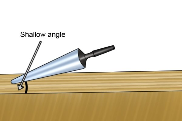 Image illustrating that a tapered spoon bit can be used effectively even when drilling at a shallow angle into a wooden workpiece
