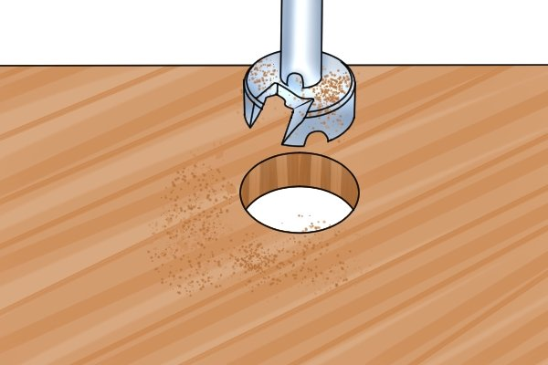 Drilling a pilot hole with a Forstner bit so that a tapered spoon bit can be inserted to widen the hole