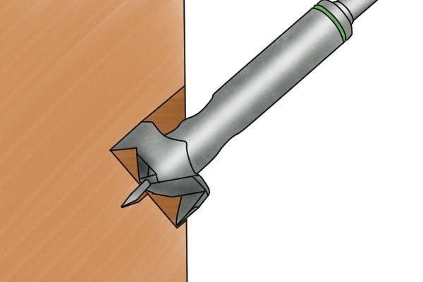 A Forstner bit drilling at an angle, which spade bits cannot do reliably unless the user has a great deal of strength to hold them in place