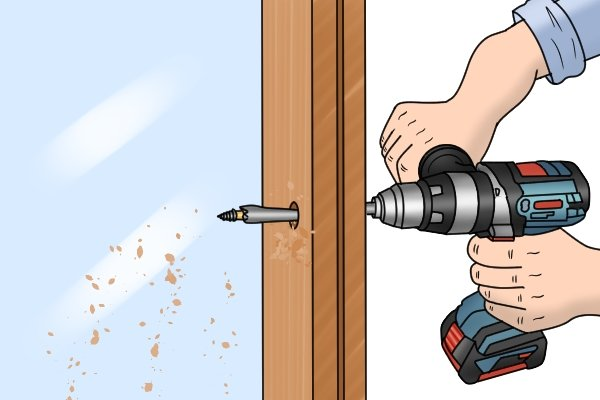 A DIYer holding onto their power drill with two hands to keep the spade bit from wrenching it out of their hands