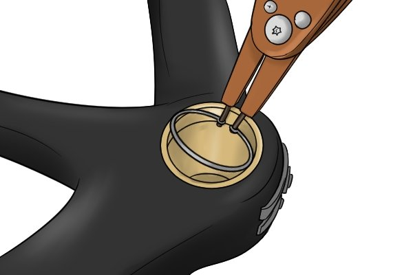 Squeeze the handles of internal circlip pliers to contract the circlip