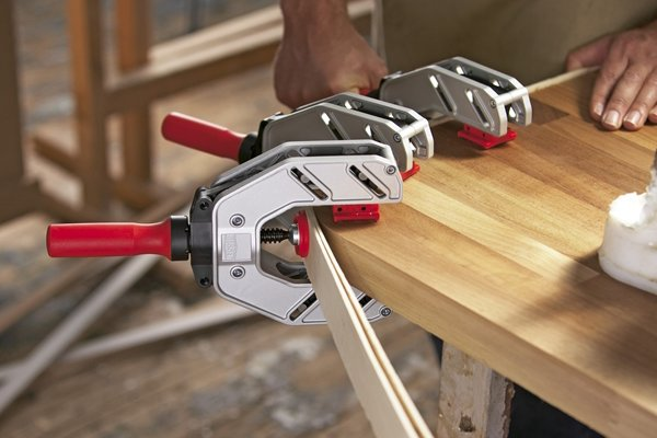 An edging clamp holds material on to an edge or corner