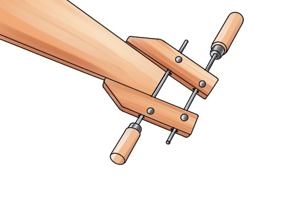 A hand screw clamp is used for clamping wood