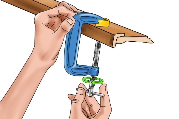 Open the clamp jaws by twisting the handle to the left
