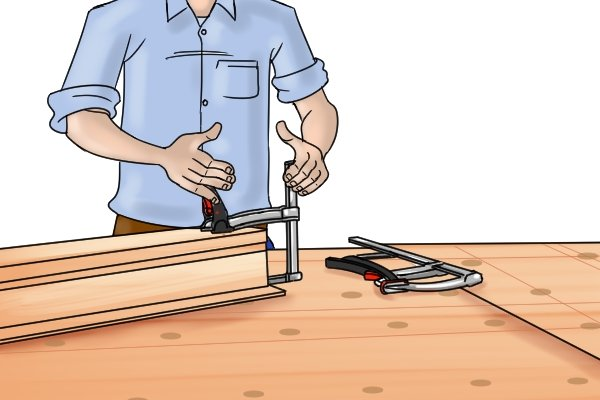 Pressing the clamp's lever to close the jaws
