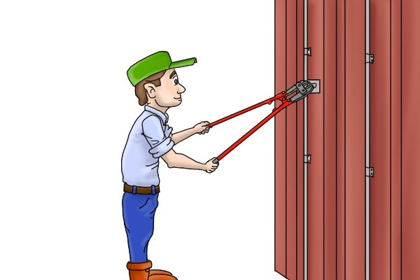 Dock worker opening sea container with bolt cutters