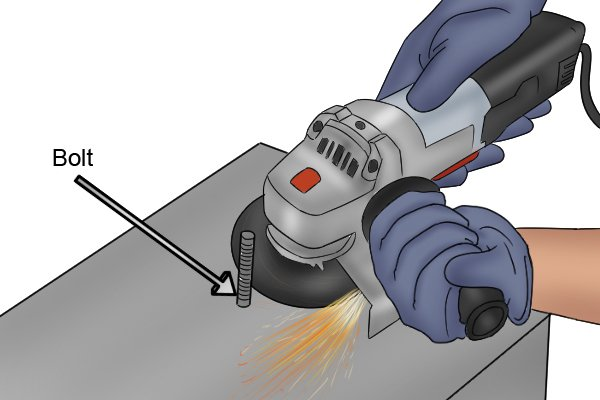 Person using an angle grinder to cut off a bolt protruding from a surface