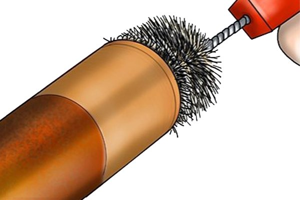 Metal pipe cleaning brush (AKA tube, spiral or twisted brush) being used to clean metal copper surfaces