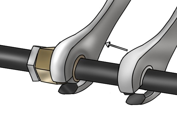 Pass pipe through opening and then slide spanner head over fastener nut.