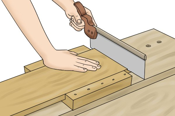 Woodworker's hand and forwards cutting action of saw keeps bench hook secure