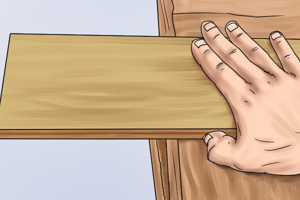 Using heel of hand and thumb to hold workpiece in bench hook
