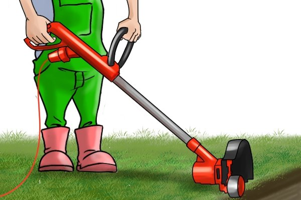Electric grass trimmer being used to trim lawn edge