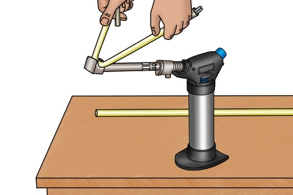Standard blow lamp with a flame extension piece and deflector being used to bend a plastic pipe.