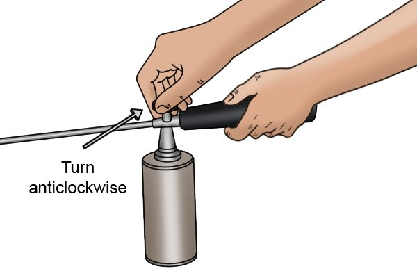 Turning the flame control valve anticlockwise to create a greater flame on a gardening blow lamp
