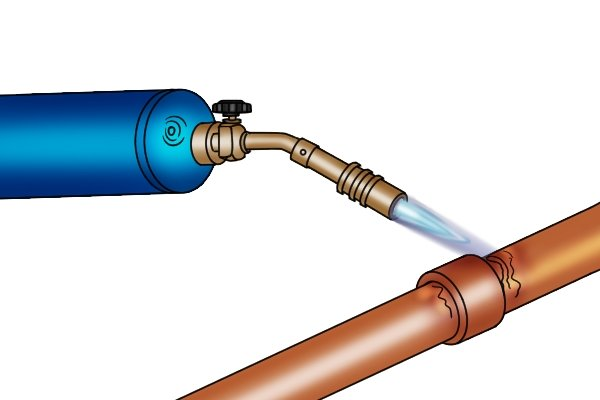 Heating a copper pipe with a heavy duty blow lamp