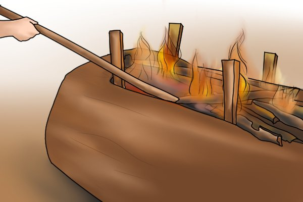 Image of a group of outdoorsmen burning out the inside of a dugout canoe