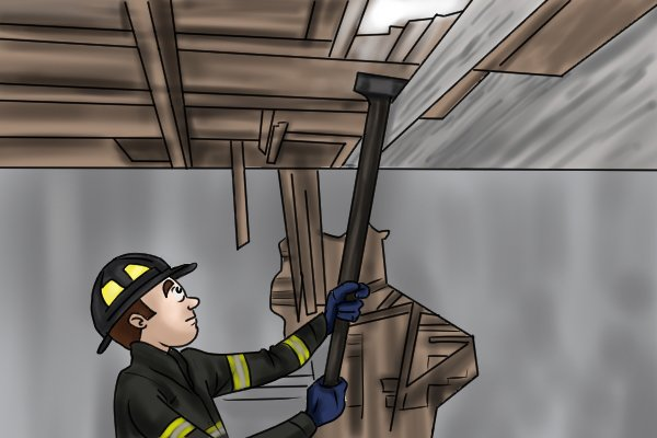 Image of a fireman using a demolition adze to bring down ceiling timbers