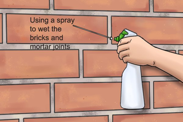 Using a spray to wet the brick and mortar joints