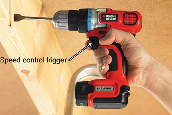 Finger pulling the speed control trigger on a cordless drill driver