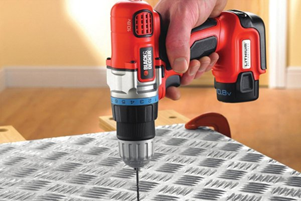 Red compact cordless drill driver drilling into a sheet of metal