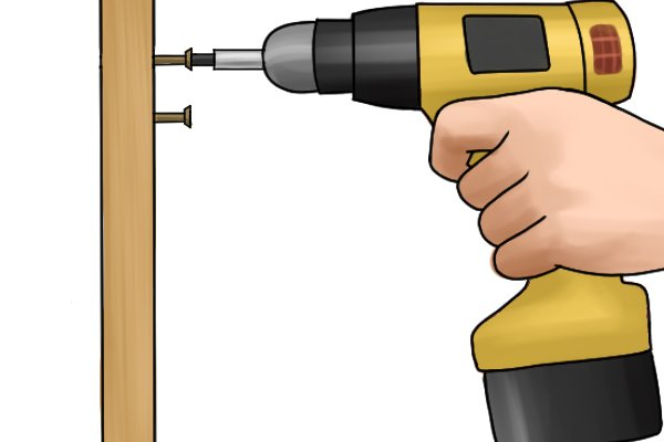 A cordless drill driver removing a screw from a piece of wood