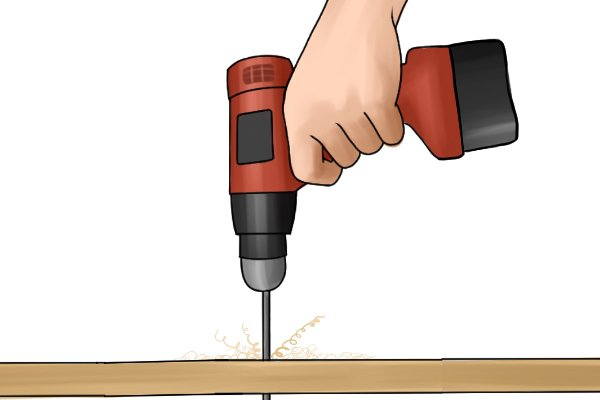 A cordless drill driver in reverse (backing out a drill bit) from a piece of wood